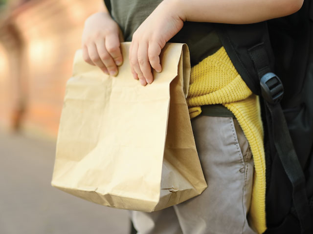 child-holding-bag-of-lunch-from-the-food-in-schools-programme-in-auckland